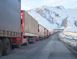 line of the trucks waiting on a road curve to cross the border in sunny winter day in mountains snowy area.