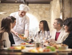 Waist-length view of a male chef displaying a dish to five smiling customers in a restaurant, West Yorkshire, England