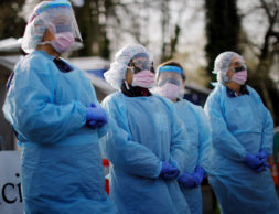 Nurses wearing protective gear wait for patients at a drive-through testing site for coronavirus disease (COVID-19) in a parking lot at the University of Washington's Northwest Outpatient Medical Center in Seattle, Washington, U.S., March 17, 2020. REUTERS/Brian Snyder