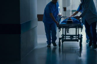 Emergency Department: Doctors, Nurses and Paramedics Push Gurney / Stretcher with Seriously Injured Patient towards the Operating Room.